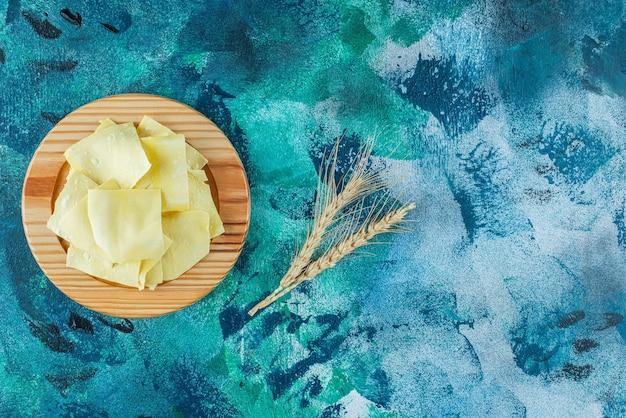 Surowa lasagne na drewnianym talerzu, na niebieskim stole.