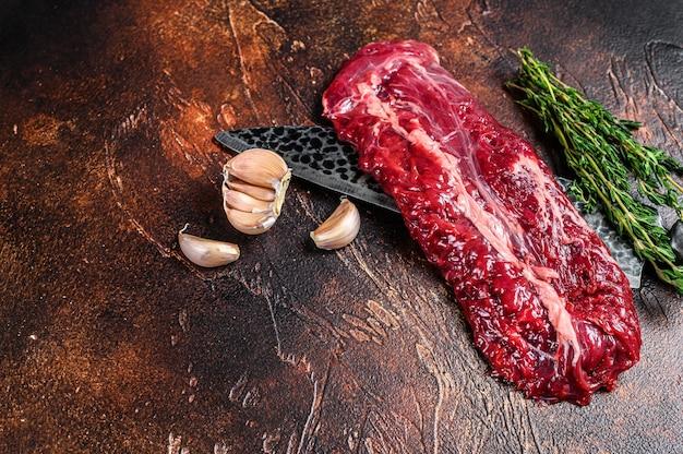 Surowa maczeta organiczna lub stek ze spódnicy na nożu rzeźniczym. ciemne tło. widok z góry. skopiuj miejsce.