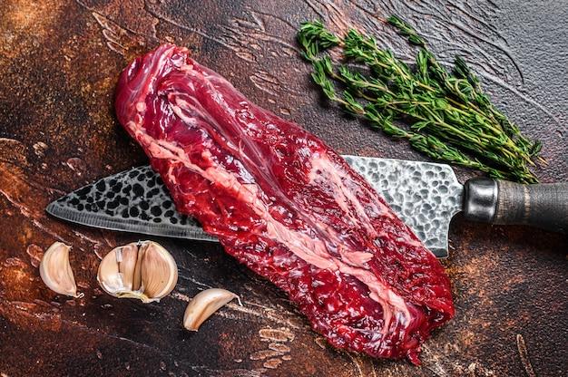 Surowa maczeta organiczna lub stek ze spódnicy na nożu rzeźniczym. ciemne tło. widok z góry.