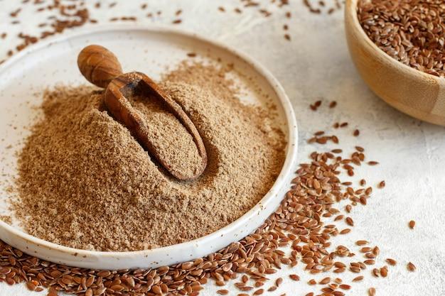 Surowa mąka z nasion lnu w talerzu ceramicznym z łyżką z bliska