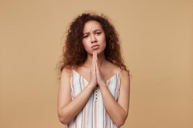 Surowa młoda ładna brązowowłosa kręcona kobieta ubrana w letni top na ramiączkach marszczy brwi, patrząc poważnie i trzymając uniesione dłonie razem, odizolowane na beżu