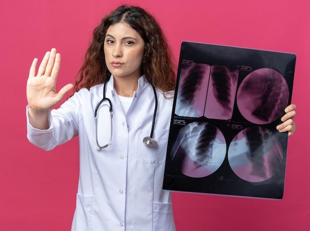 Surowa młoda lekarka ubrana w szatę medyczną i stetoskop pokazujący zdjęcie rentgenowskie, robiąc gest zatrzymania na białym tle na różowej ścianie