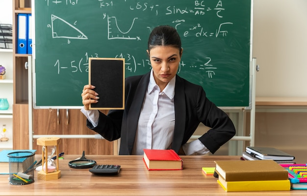 Surowa młoda nauczycielka siedzi przy stole z przyborami szkolnymi, trzymając w klasie mini tablicę