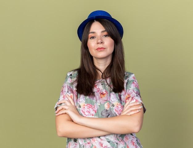 Surowa młoda piękna dziewczyna w kapeluszu imprezowym, krzyżująca ręce