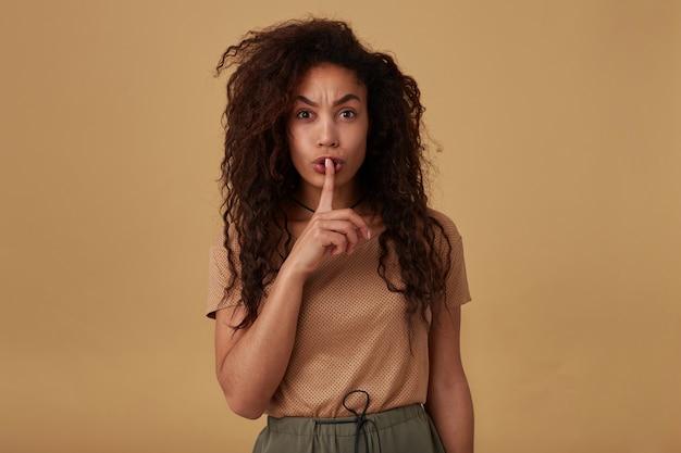 Surowa młoda śliczna ciemnoskóra brunetka kobieta z kręconymi luźnymi włosami podnosząca rękę w cichym geście i wyglądająca poważnie, odizolowana na beżu