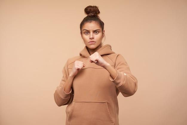 Surowa młoda zielonooka brunetka kobieta z fryzurą kok, patrząc poważnie z przodu i trzymając uniesione pięści, pozując na beżowej ścianie w sportowym ubraniu