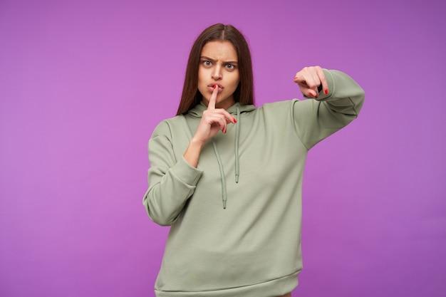 Surowa, młoda zielonooka brunetka kobieta z luźnymi włosami, skierowana krzyżowo z przodu, prosząca o ciszę, trzymając palec wskazujący podczas pozowania nad fioletową ścianą