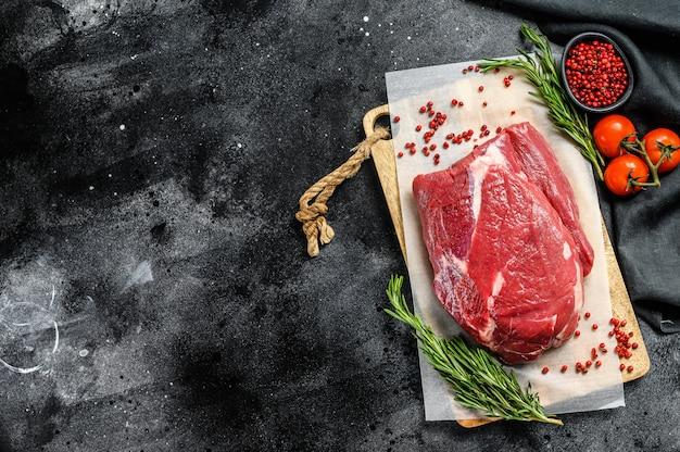Surowa mostek wołowy cięty na drewnianej desce do krojenia na czarnej angus wołowiny na czarny stół