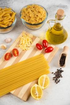 Surowa odmiana makaronu, oleju i świeżych warzyw na marmurze.