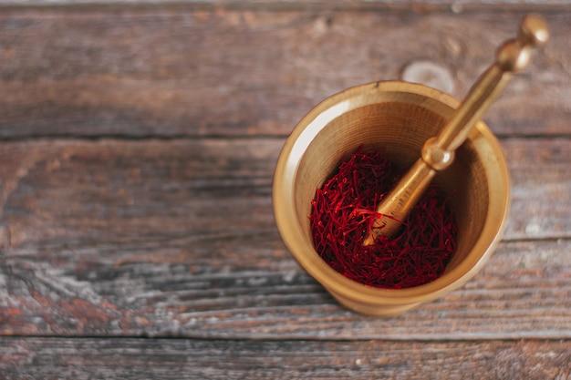 Surowa organiczna przyprawa z czerwonego suszonego szafranu na drewnianym stole w mosiężnym moździerzu z rocznika metalowym z tłuczkiem.