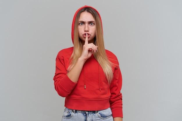 Surowa piękna blond młoda kobieta z piegami wykonuje gest ciszy, prosi, by nie zdradzić nikomu jej sekretu przez szarą ścianę koncepcja ciszy