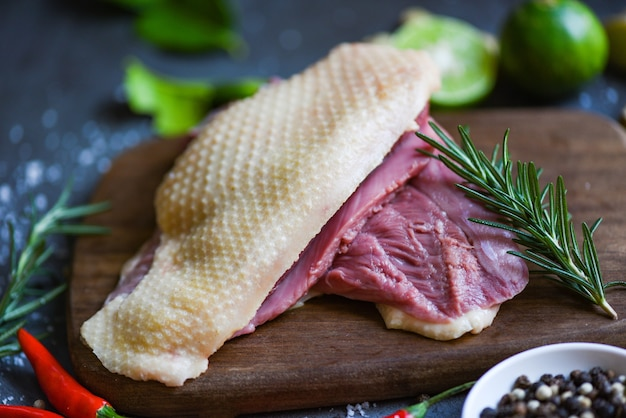 Surowa pierś z kaczki z przyprawami ziołowymi na ciemnym tle, świeże mięso kaczki na żywność