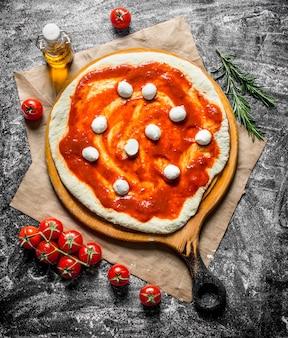 Surowa pizza. rozwałkowane ciasto z mozzarellą i koncentratem pomidorowym na rustykalnym stole