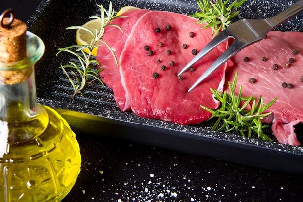 Surowa pokrojona wołowina na garnku talerzowym na czarnym tle