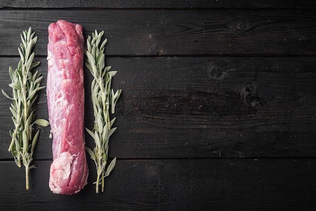 Surowa polędwica wieprzowa. świeże mięso ze składnikami i ziołami do grillowania lub pieczenia, szałwia, zestaw ziemniaków, na tle czarnego drewnianego stołu, widok z góry płaski, z copyspace i miejscem na tekst