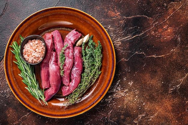 Surowa polędwiczka jagnięca filet mięso w rustykalnym talerzu z tymiankiem i rozmarynem. ciemne tło. widok z góry. skopiuj miejsce.