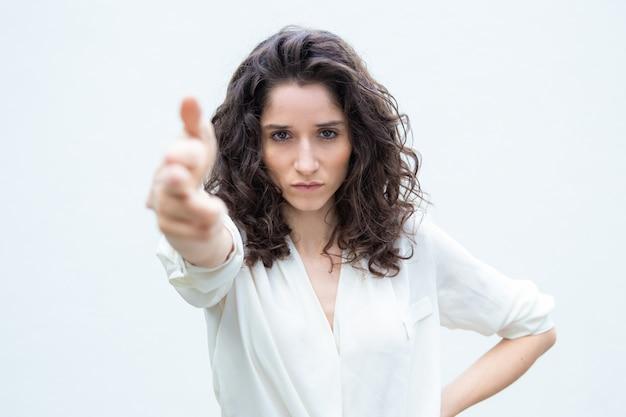 Surowa poważna kobieta robi ręka pistoletu strzału gestowi
