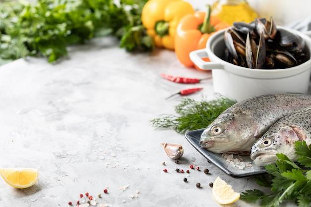Surowa pstrąg tęczowy na talerzu, warzywa i świeże warzywa do przygotowania zdrowego i smacznego jedzenia. biała patelnia z małżami na betonie