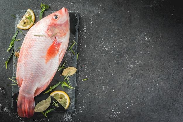 Surowa ryba czerwony tilapia na desce do krojenia na czarnym kamiennym stole, z przyprawami, cytryną i ziołami do gotowania. widok z góry copyspace