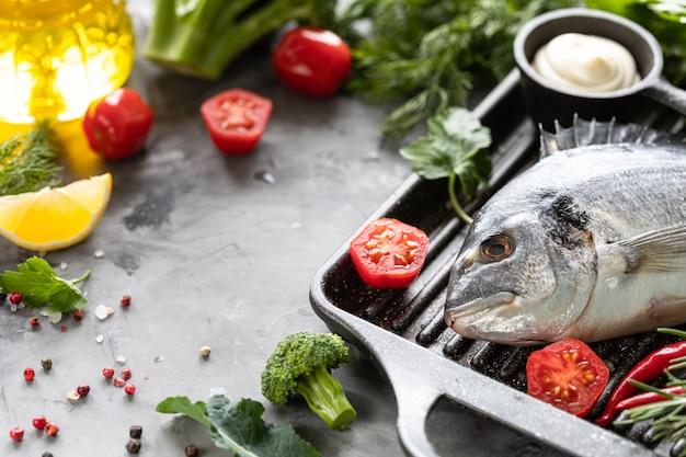 Surowa ryba dorado z przyprawami, cytryną i natką pietruszki na czarnej patelni grillowej na białym betonie
