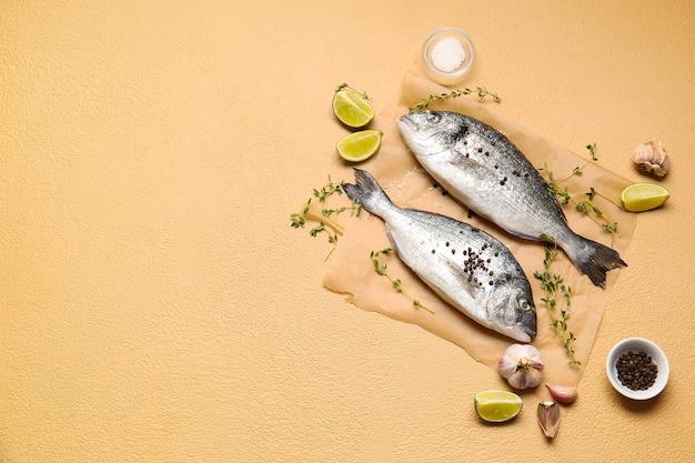 Surowa ryba dorado z przyprawami na beżu