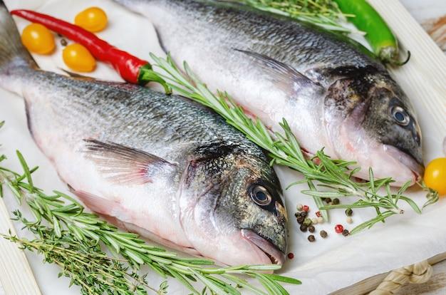 Surowa ryba dorado z ziołami przygotowana do gotowania