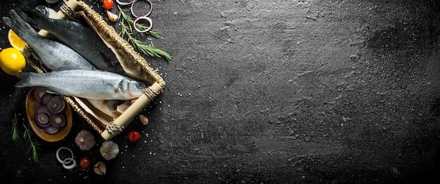 Surowa ryba labraksa w koszu z cytryną i posiekaną cebulą. na czarnym tle rustykalnym