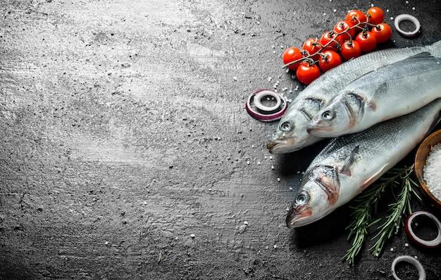 Surowa ryba labraksa z pomidorami, rozmarynem i krążkami cebulowymi. na czarnym tle rustykalnym