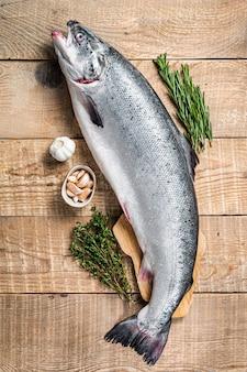 Surowa ryba łososia morskiego na drewnianym stole kuchennym z ziołami
