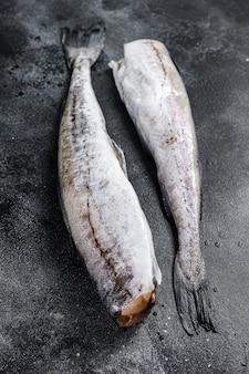 Surowa ryba mintaja gotowa do przyrządzenia. czarne tło. widok z góry.