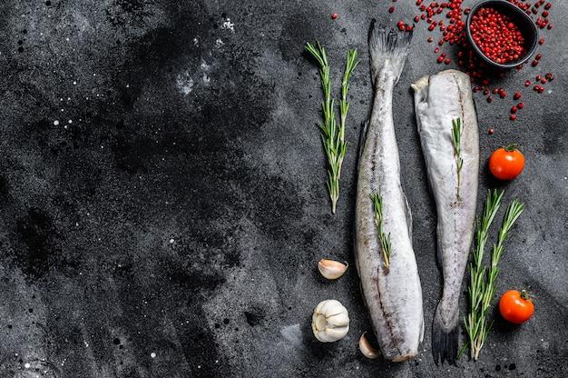 Surowa ryba mintaja z rozmarynem i różowym pieprzem. organiczne owoce morza. czarna przestrzeń. widok z góry. skopiuj miejsce