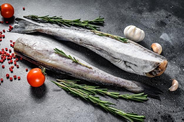 Surowa ryba mintaja z rozmarynem i różowym pieprzem. organiczne owoce morza. czarna przestrzeń. widok z góry