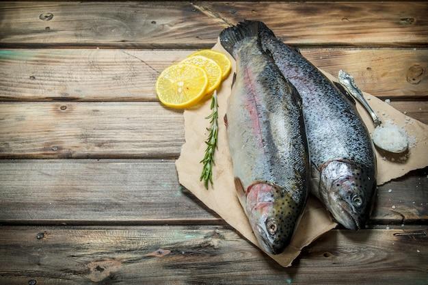 Surowa ryba morska z ziołami i ćwiartkami cytryny. na drewnianym