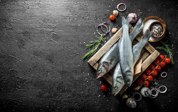 Surowa ryba na drewnianej tacy z pomidorami, przyprawami, czosnkiem, rozmarynem i krążkami cebulowymi.