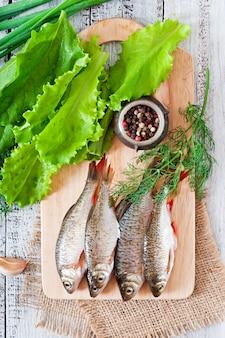 Surowa ryba na drewnianej tnącej desce, odgórny widok