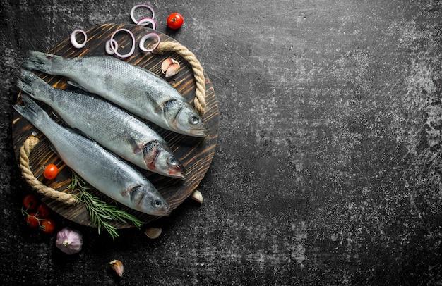 Surowa ryba na tacy z pokrojoną cebulą, rozmarynem i pomidorami.
