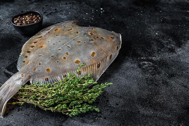 Surowa ryba płastugi flądry na marmurowej desce z tymiankiem