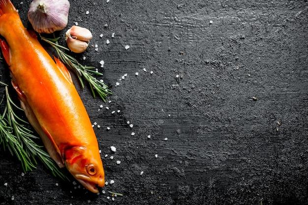 Surowa ryba pstrąg z rozmarynem i czosnkiem na czarnym rustykalnym stole.