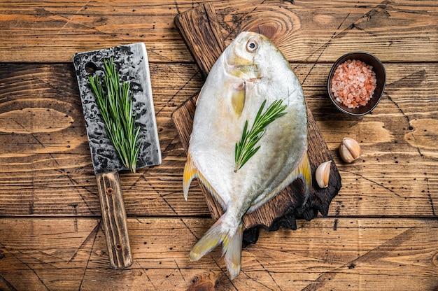 Surowa ryba samogłów lub pompano na desce