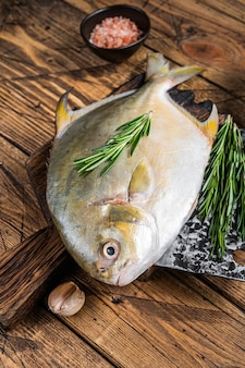 Surowa ryba samogłowa lub pompano na drewnianej desce