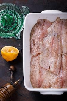 Surowa ryba z cytryną, przygotowywająca dla pieczenia. tilapia.selective ostrość