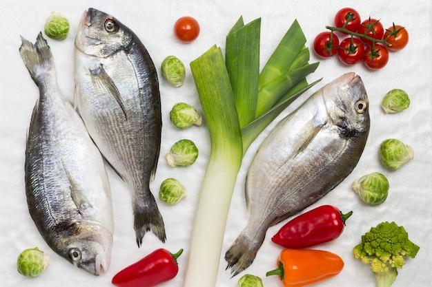 Surowa ryba z kolorowymi warzywami.