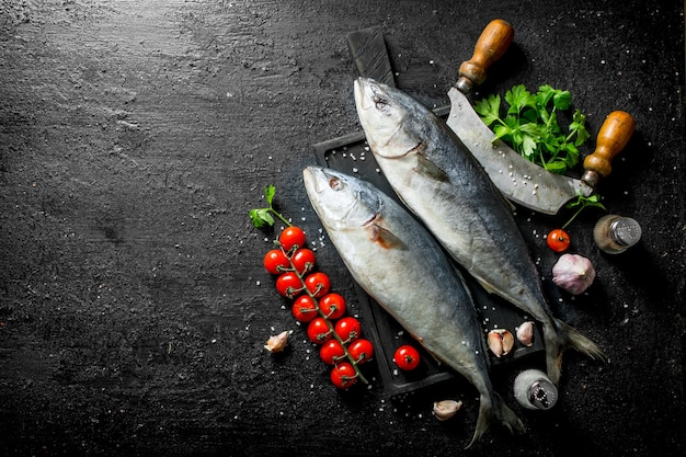 Surowa ryba z nożem, pomidorami i pietruszką. na czarnym tle rustykalnym