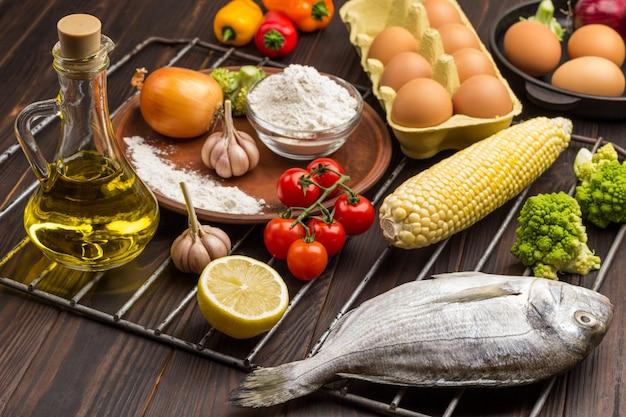 Surowa ryba z warzywami na ruszcie grillowym. jajko i mąka, butelka z olejem.