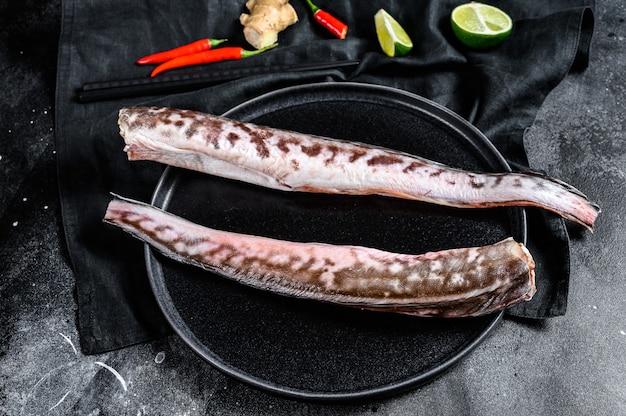 Surowa ryba z węgorza morskiego z dodatkami do gotowania, limonka, imbirowa papryczka chili
