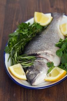 Surowa ryba z ziele i cytryną na naczyniu na drewnianej powierzchni