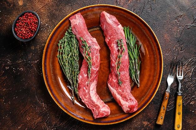 Surowa spódnica maczeta stek wołowy na talerzu. ciemne tło. widok z góry.