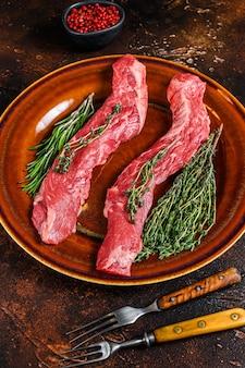 Surowa spódnica maczeta wołowiny stek na talerzu. ciemne tło. widok z góry.