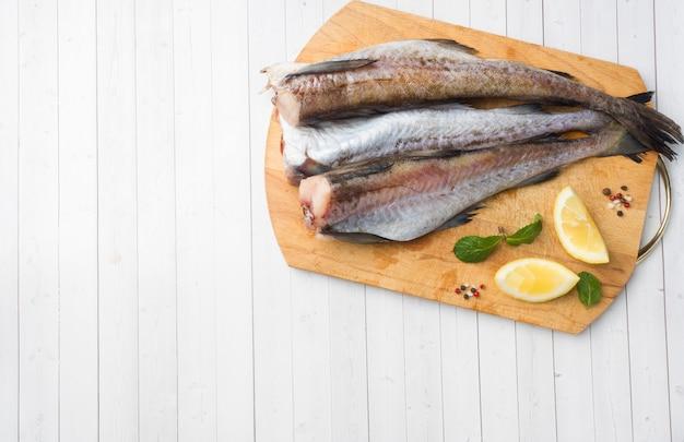 Surowa świeża ryba pollock na drewnianej desce z cytryną kopiuje przestrzeń