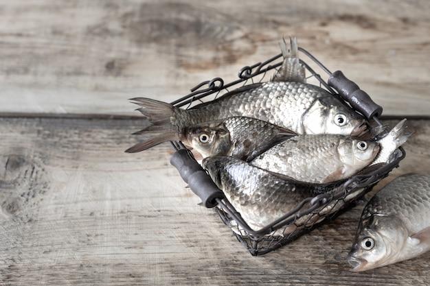 Surowa świeża rzeki ryba w pucharze na drewnianym stole